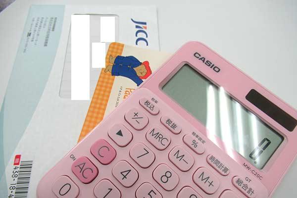 JICCの封筒と電卓と通帳